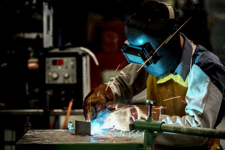 Industrial welding worker at the factory, welding steel with safety protective mask Stock Photo