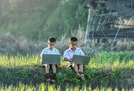 Two boys using a laptop outdoors