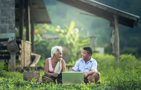 Happy boy and grandmother using a laptop outdoors Foto de archivo