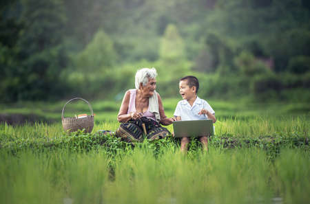 Happy boy and grandmother using a laptop outdoors Standard-Bild