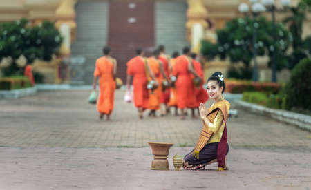 harity event: Woman give food offerings to Buddhist monks Stock Photo