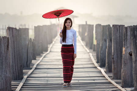 Burmese woman holding traditional red umbrella and walking on U Bein Bridge 免版税图像