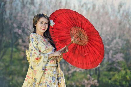 魅力的なアジアの女性の赤い傘と伝統的な日本の着物を着て