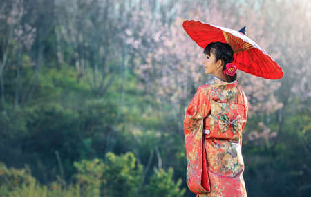 Asian woman wearing traditional japanese kimono, sakura background Imagens