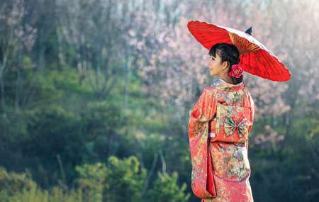Aziatische vrouw die traditionele Japanse kimono, Sakura achtergrond draagt