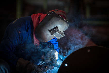 Industrial welding worker at the factory, welding steel joint with safety protective mask photo