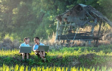 Deux garçons étudient par apprentissage en ligne avec un ordinateur portable à l'extérieur, campagne de Thaïlande Banque d'images - 75554450