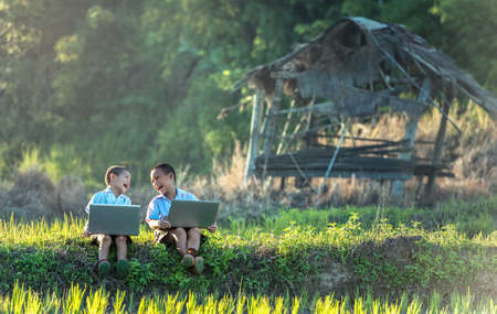 Two boys studying by online learning with laptop at outdoor, countryside of Thailand 免版税图像