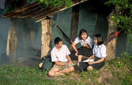 happy asian people: Education, Student, People concept - Group of Asian students in uniform studying together at outdoor. Asian students looking happy to study.