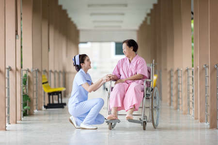 Senior vrouw in rolstoel praten met een verpleegster in een ziekenhuis
