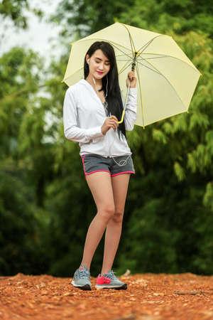 gotas de agua: Mujer asiática escuchando música con un paraguas