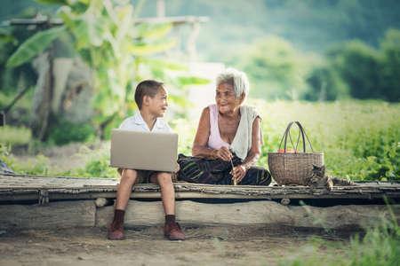 행복한 소년과 할머니가 노트북을 사용하여 스톡 콘텐츠
