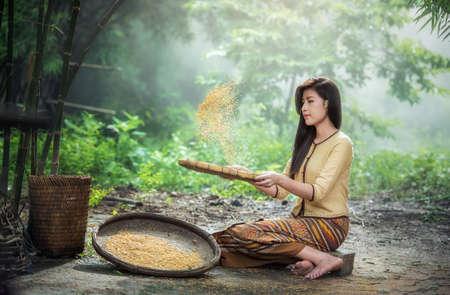 Beautiful girl winnowing rice separate between rice and rice husk