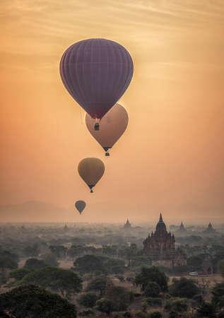 霧の深い朝、ミャンマーのバガンの平野を熱気球 写真素材