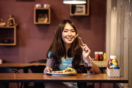 Woman eating steak in a restaurant Stock Photo