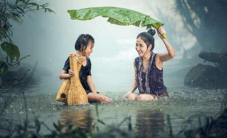 Aziatische zus in de regen, platteland van Thailand