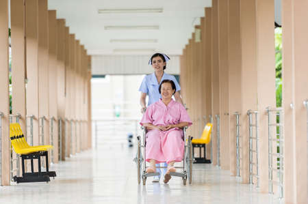 휠체어에 수석 여자 환자를 운반 해피 간호사