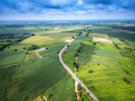Aerial view of a country road amid fields with a white car Stock Photo - 75710564