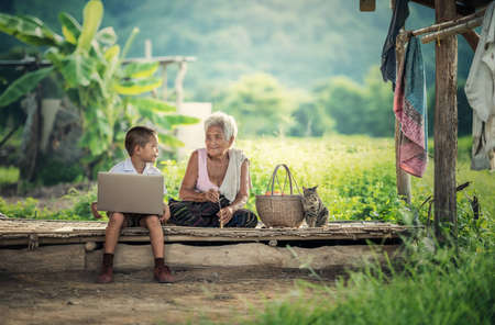 Happy boy and grandmother using laptop Standard-Bild