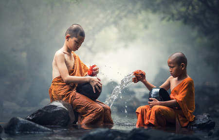Asian Novice monks cleaning alms bowl in creeks Stock Photo