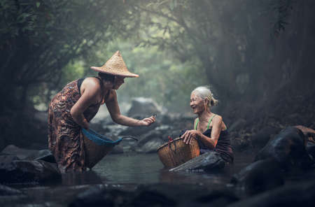 Old Asian woman working in creek Stock Photo