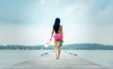 Young woman walking with beer bottle on pier,remote tropical beaches and countries. travel concept