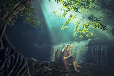 アジアの女性の滝、タイで一人で座って 写真素材