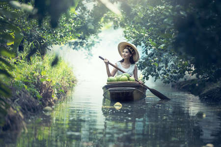 Young smiling agriculture woman worker on the boat and grapefruit harvest in garden