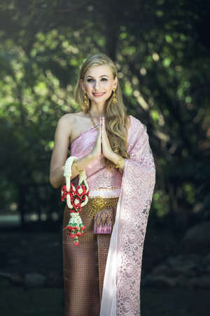 Caucasian Woman wearing typical,traditional Thai dress with identity Thai culture Sawasdee,Welcome expression Sawasdee, Thailand