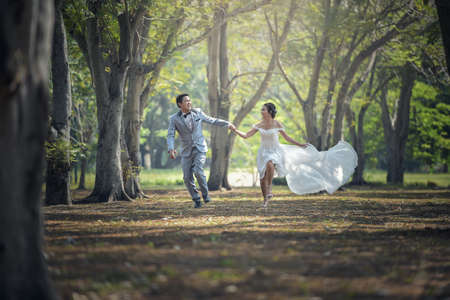 Bride and groom running and park and holding hands Stock Photo