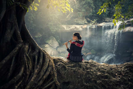 synonym: Girl plays the wood flute in nature backgrond