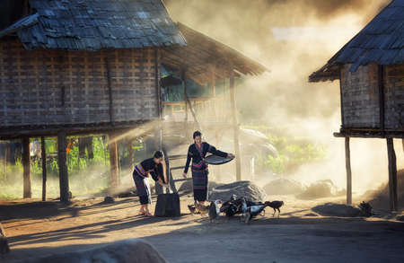 Aziatische meisjes voeren kippen op Laos platteland Stockfoto