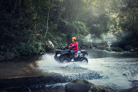 山の道を ATV クワッド バイクの女性