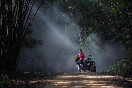 brunett: Elegant woman riding quadricycles ATV in forest Stock Photo