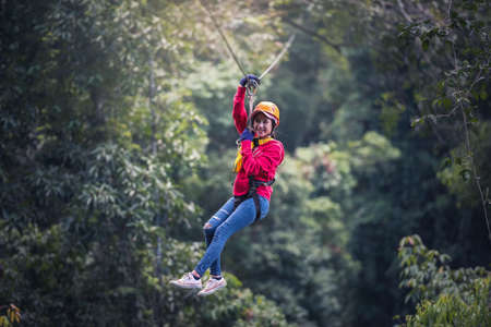 ラオスの熱帯雨林、アジアでジップ ・ ラインやキャノピーの経験にカジュアルな服を着ている女性観光 写真素材