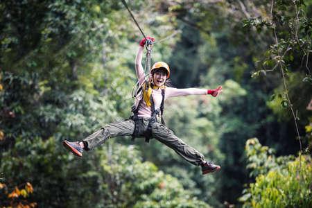 라오스 열대 우림, 아시아에서 지퍼 라인 또는 캐노피 경험에 캐주얼 의류를 입고 여자 관광객 스톡 콘텐츠