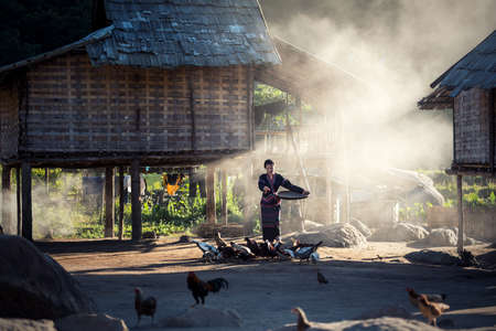 Asian girls feeding chickens at Laos countryside Stock Photo
