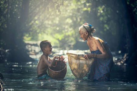 Asian Grandmother and her child are fishing in the creek at countryside of Thailand