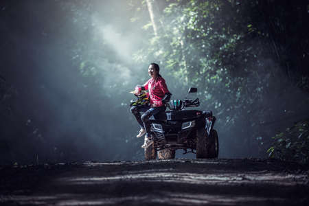 Elegant woman riding quadricycles ATV in forest Zdjęcie Seryjne
