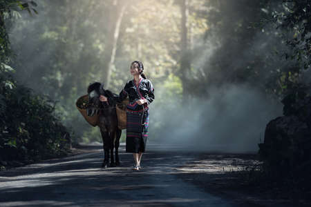 Asian woman worker with her donkey in forest countryside of Thailand
