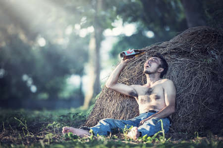 intoxicated: Alcohol addicted man sitting alone with alcohol bottle Stock Photo