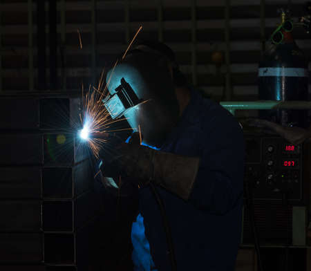 Industrial Worker at the factory welding, welding steel structure