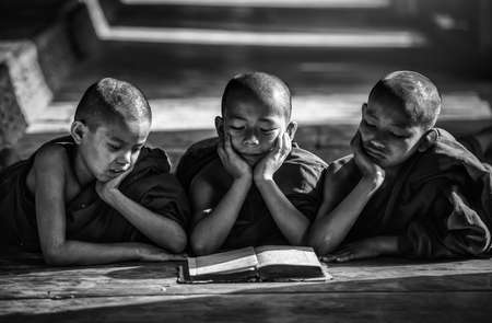 Novice monk reading book,in monastery, Bagan, Myanmar (Black and white tone)