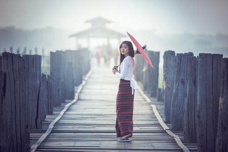 ビルマ女性伝統的な赤い傘を押しながら U Bein 橋、ミャンマーの上を歩く 写真素材
