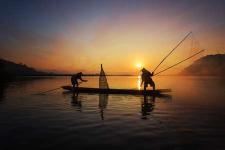 Silhouette of Asian fisherman on wooden boat in action casting a net for catching freshwater fish in nature river in the early morning before sunrise Zdjęcie Seryjne