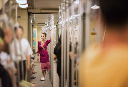 Asian woman with traditional dress in the train, Bangkok, Thailand, Concept Working woman
