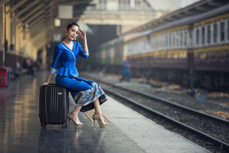Passenger traveler woman in train station waiting for travel. Young business woman smiling sitting with travel suitcase trolley, in waiting hall of departure lounge in train station. Zdjęcie Seryjne