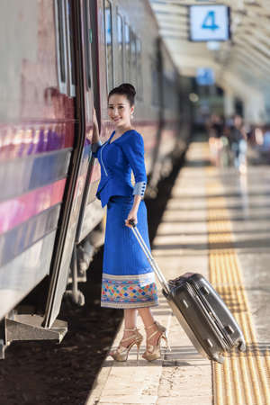 Traveler girl walking and waits train on railway platform Zdjęcie Seryjne
