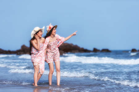 Beautiful friends enjoying a walk on the beach on a sunny day. Two young women walking together on a beach