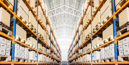 Rijen van planken met dozen in moderne magazijn Stockfoto